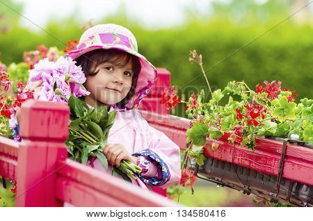 The little girl close in a pink hat and a raincoat. green background. Sweet toddler girl with pink flowers on red bridge