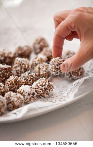 White plate full of delicious raw protein balls. Healthy sweets for sport people. A hand taking homemade dessert.