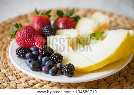Cut melon and berries. Fruit salad of strawberries blueberries melon mint and blackberries. Diet salad on the white plate - breakfast weight loss concept. closeup. Healthy snack.