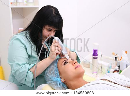 Woman receiving cleansing therapy with a professional ultrasonic equipment in cosmetology office