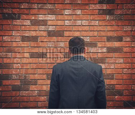 A business man has his back turned and looking at a brick wall. Can represent an obstacle sadness or a struggle.