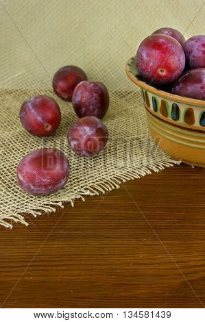 Sweet plums on wooden background. Organic fruits.