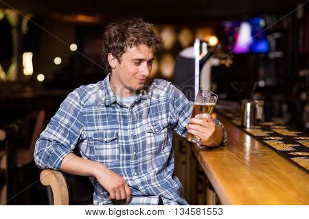 Single Man Sitting At Bar Having A Beer