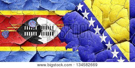 Swaziland flag with Bosnia and Herzegovina flag on a grunge crac