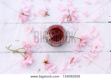 Beautiful floral background with Spring flowers and raspberry jam jar