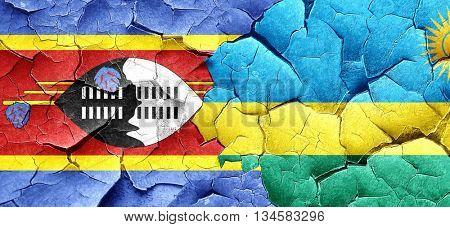 Swaziland flag with rwanda flag on a grunge cracked wall