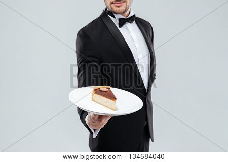 Butler in tuxedo with bowtie holding plate with piece of cake