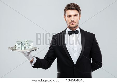 Handsome young waiter in tuxedo standing and holding money on tray