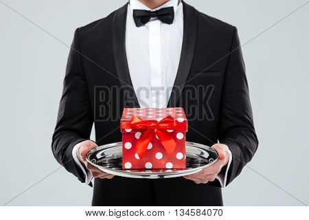 Closeup of butler in tuxedo holding tray with gift box