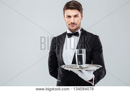 Portrait of waiter in tuxedo and gloves holding glass of water on metal tray