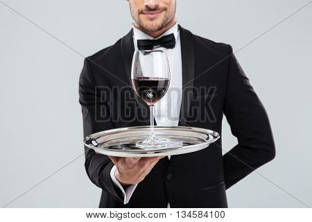 Closeup of young butler in tuxedo holding silver tray with glass of red wine
