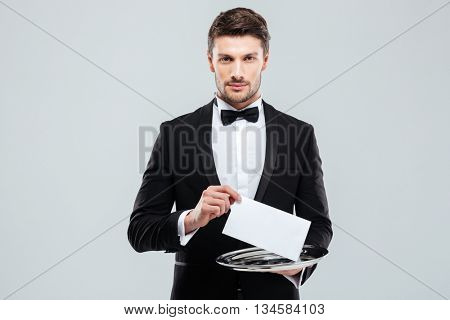 Handsome young waiter in tuxedo holding tray with blank card