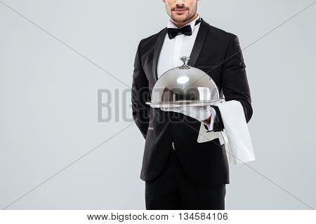 Closeup of butler in tuxedo and gloves holding silver tray with lid and napkin