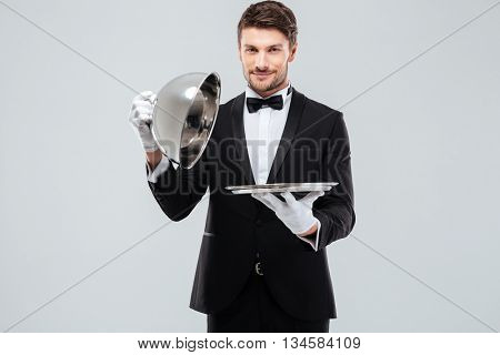 Handsome young butler in tuxedo with bowtie holding and opening metal tray with lid