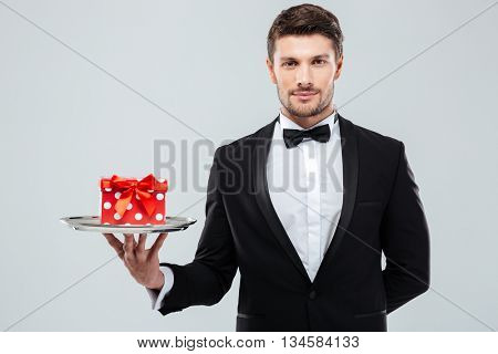 Attractive young waiter in tuxedo with bowtie holding present box on tray