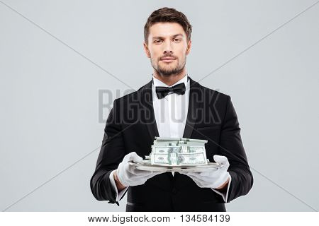 Attractive young butler in tuxedo and gloves holding money on tray
