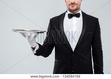 Closeup of young waiter in tuxedo and gloves holding silver tray