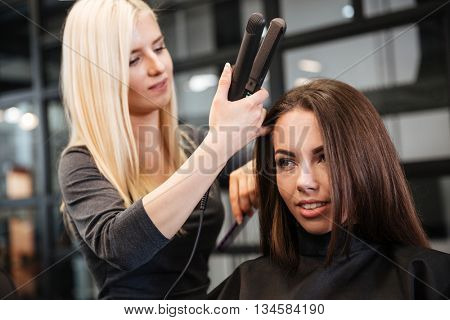 Beautiful hairstylist curling hair woman client in hairdressing beauty salon