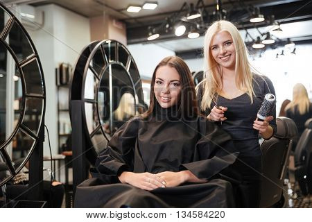 Beautiful blonde female hairdresser holding scissors and comb looking at camera