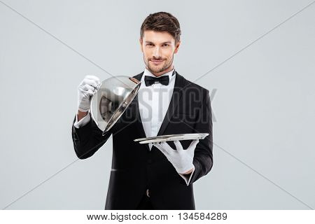 Happy young waiter in tuxedo and bowtie lifting metal cloche from serving tray