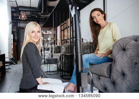 Attractive female pedicurist with a friendly smile doing a pedicure in a beauty salon