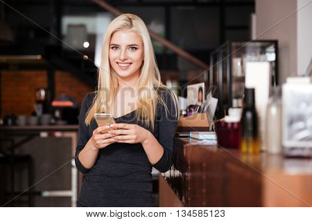 Young female receptionist of beauty salon with smartphone