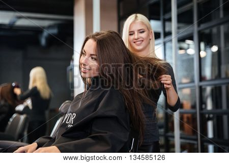 Young stylist drying woman hair in beauty salon
