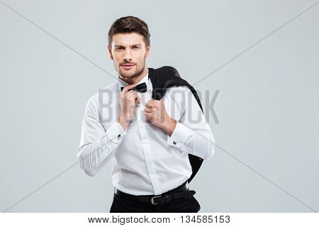 Man in tuxedo with bowtie standing and holding his jacket