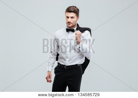 Handsome young man in tuxedo with bowtie holding his jacket