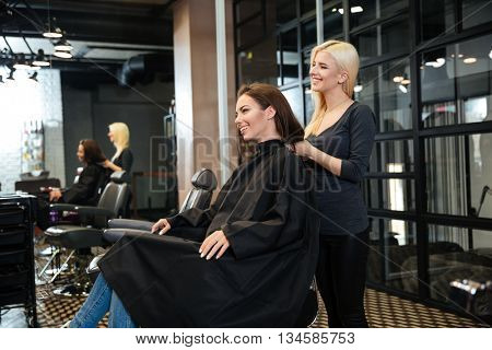 Young smiling girl sitting at the beauty salon and talking with female hairdresser