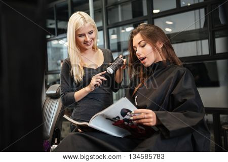 Young beautiful woman discussing hairstyling with her hairdresser while sitting in the hairdressing salon