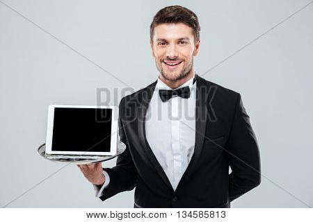 Cheerful young waiter in tuxedo standing and holding blank screen tablet on tray