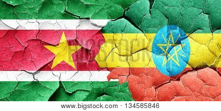 Suriname flag with Ethiopia flag on a grunge cracked wall