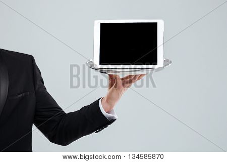 Hand of waiter in black suit holding blank screen tablet on tray