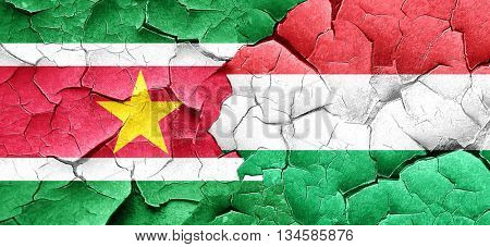 Suriname flag with Hungary flag on a grunge cracked wall