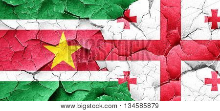 Suriname flag with Georgia flag on a grunge cracked wall