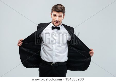 Smiling young man in tuxedo with bow tie taking off his jacket