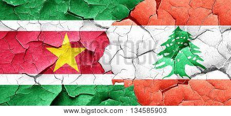 Suriname flag with Lebanon flag on a grunge cracked wall