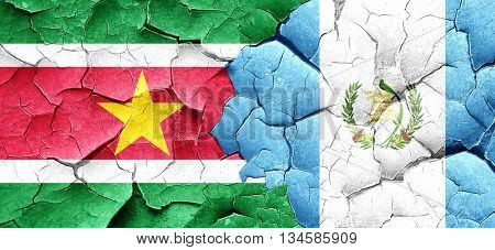 Suriname flag with Guatemala flag on a grunge cracked wall