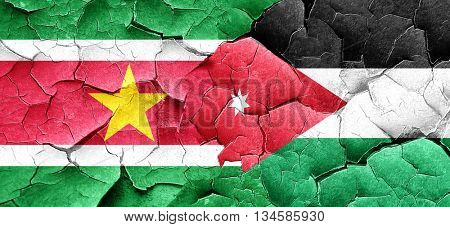 Suriname flag with Jordan flag on a grunge cracked wall