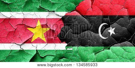 Suriname flag with Libya flag on a grunge cracked wall