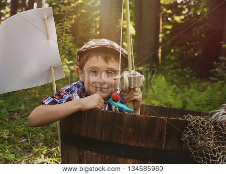 A little boy is pretending to fish in a wooden barrel boat in the nature woods with a toy fish being caught by the child for an imagination or creativity concept.