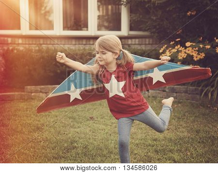 A little child is wearing homemade cardboard flying wings with stars on them pretending to be a pilot for a craft imagination or exploration concept.