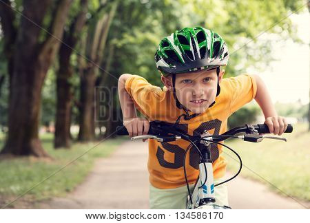 Speedy little racer on the bicycle in summer park