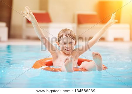 Happy boy swimming in the pool on the lifebuoy