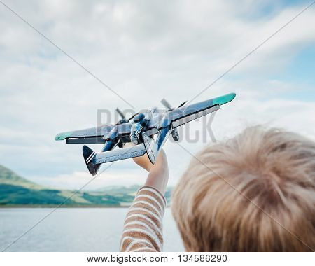Child hand with toy airplane against lake background