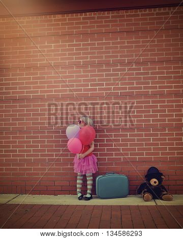A little girl is holding colorful balloons against a brick wall with a vintage suitcase and teddy bear for a travel creativity or happy concept.