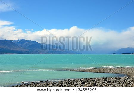 Spectacular turquoise waters of Lake Pukaki with grey gravel shore in the foreground and mountains and clouds in the distance, South Island of New Zealand