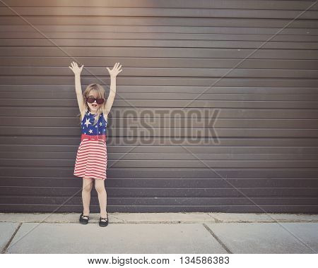 A little girl is wearing glasses standing outside against a wall with her arms up for a freedom happiness or excitement idea