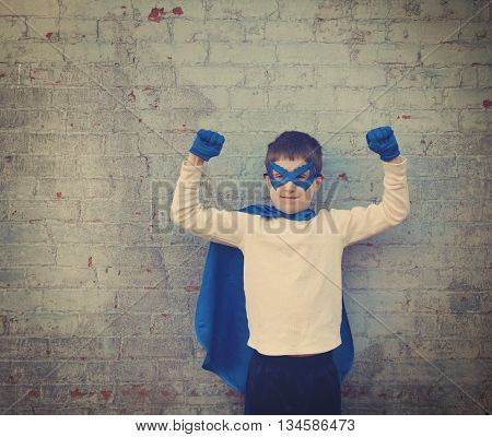 A photo of a vintage child dressed up as a super hero with his strong arms up for a confidence bravery or imagination concept.